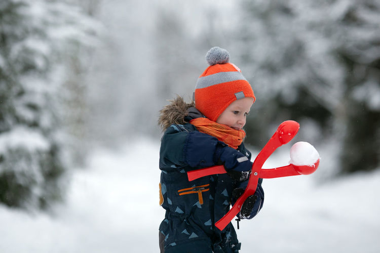 Boy standing on snow during winter