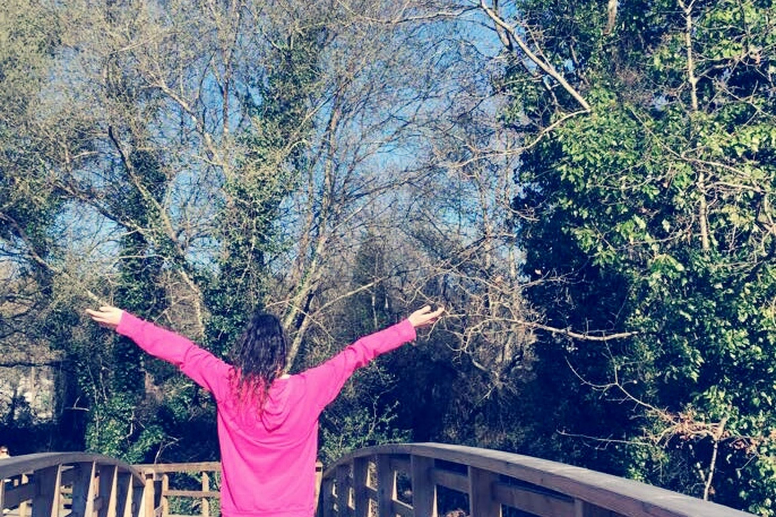 lifestyles, tree, leisure activity, person, casual clothing, water, standing, waist up, railing, day, three quarter length, outdoors, branch, holding, nature, young women, young adult, red