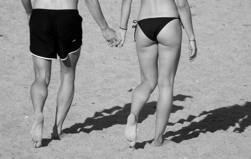 Low section of couple holding hands while walking at beach during sunny day