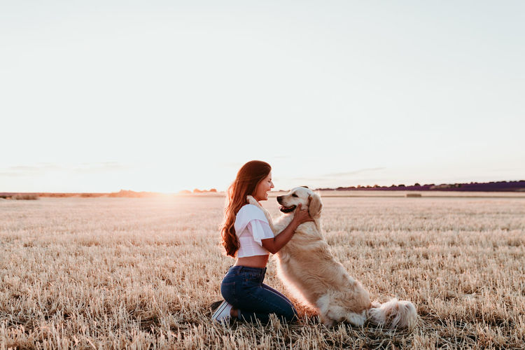 Woman with dog on field against clear sky