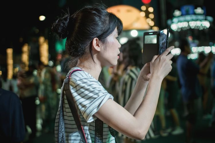 Side view of young woman photographing on mobile phone at night