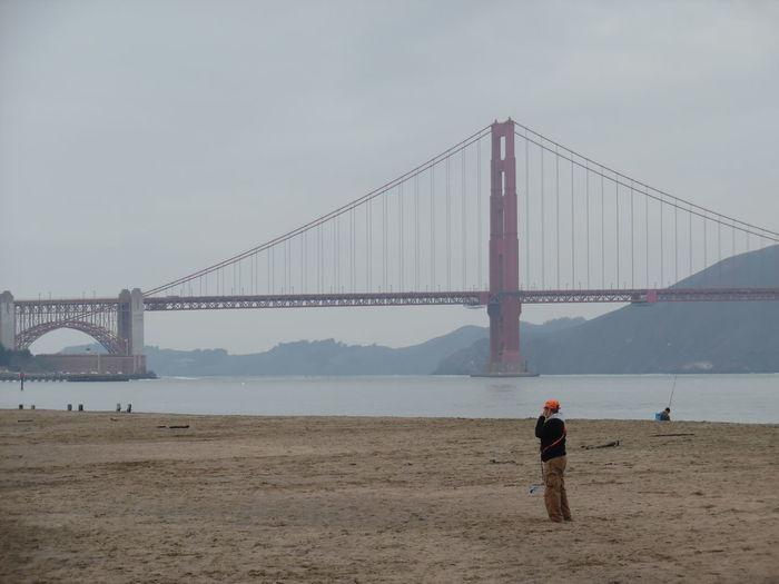Man standing at beach against golden gate bridge