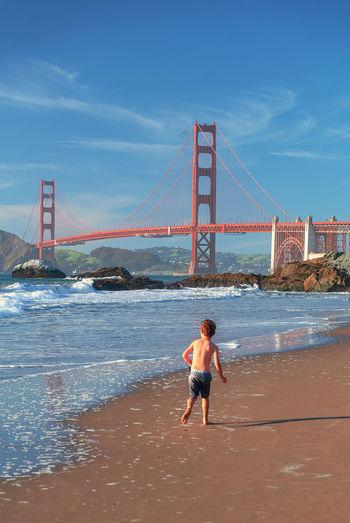 Full length of man on bridge over sea against sky