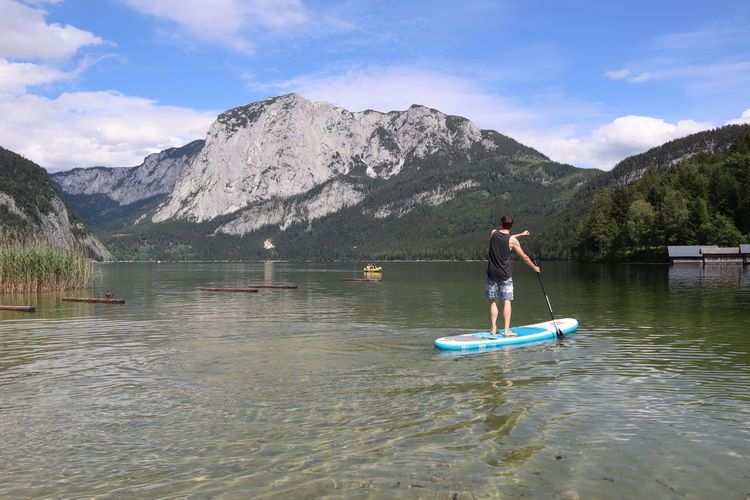 Man standing on paddleboard in lake against mountain