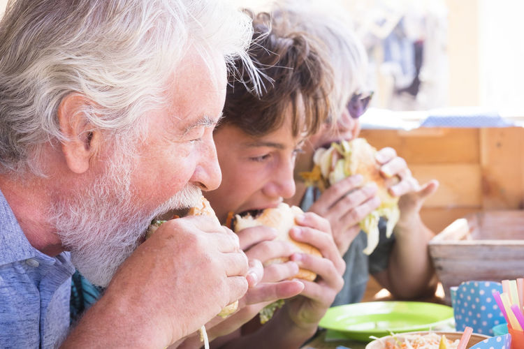 Family eating burgers at restaurant