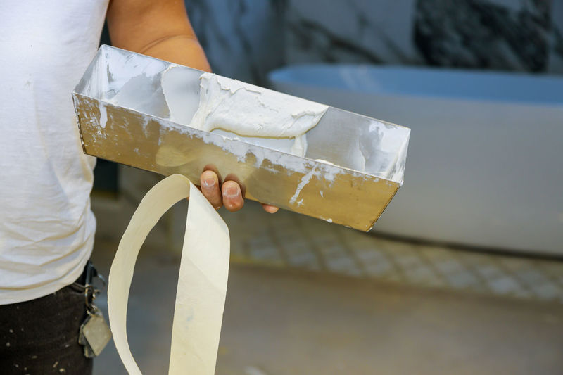 Midsection of mason holding plaster outdoors