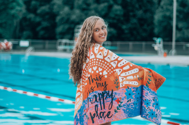 Portrait of smiling young woman wrapped in towel standing by swimming pool