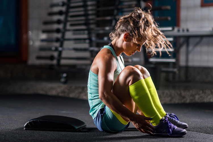 Mid Adult Woman Sitting On Floor In Gym