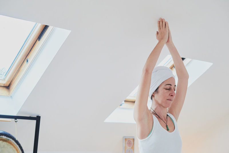 Woman with arms raised against white wall