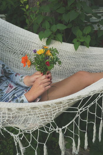 Midsection of woman holding flower bouquet while relaxing in hammock