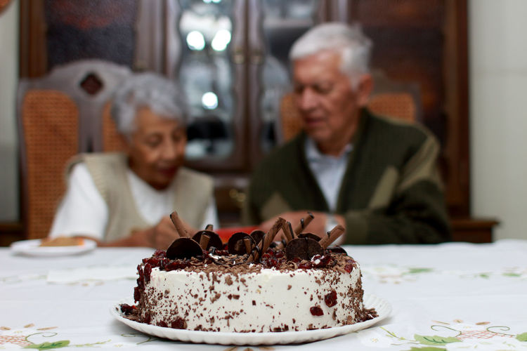 Close-up of cake with senior couple in background