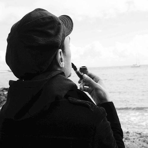 Rear View Of Man Smoking With Pipe Against Sea