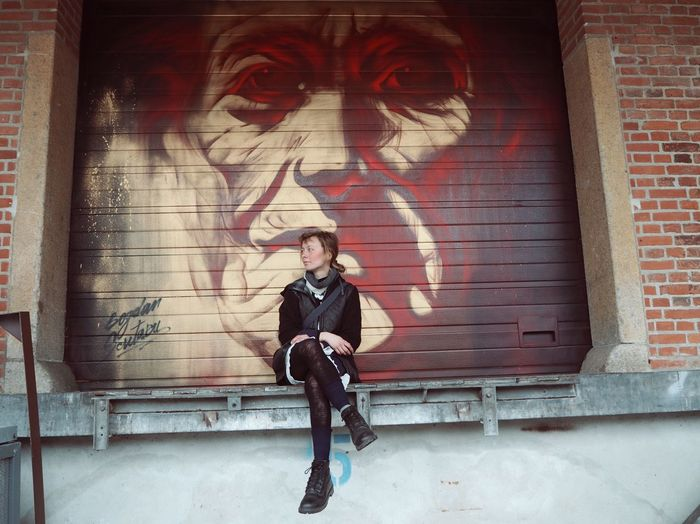 Full length of young woman sitting against graffiti wall