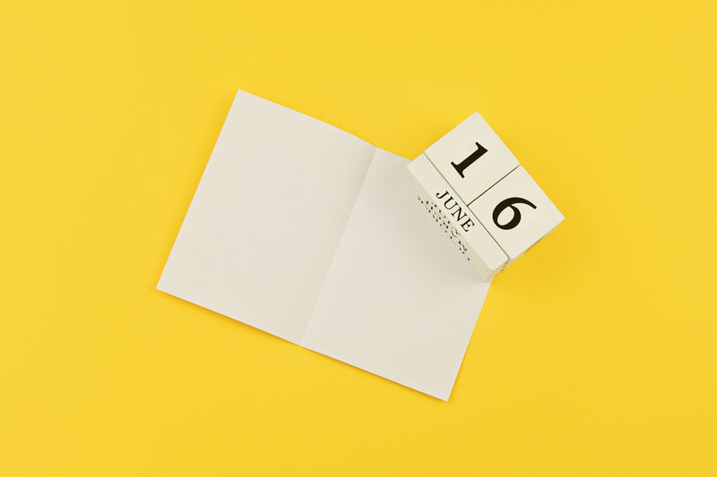 Flat lay with vintage wooden block calendar and white empty blank on a yellow background to celebrate Happy Fathers Day with date 16st June. Greeting card concept to celebrate Father's day Fathers Day Father Calendar Happy Blank Template Mock Up Gift Dad Greeting Celebration Card Holiday Concept Man Event Daddy Papá Object Yellow Celebrate Fatherhood  Flat Lay Lifestyle Congratulation Note Date Empty Paper White Sheet Block Celebrating Concepts Craft Cube Daily Handmade Minimalism Mockup Number Planning Vintage Wooden 16th June Open Studio Shot Copy Space Still Life High Angle View Single Object