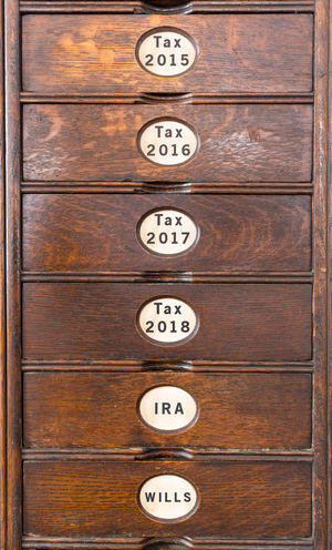 Old retro wooden filing cabinet with drawers and labels for tax and financial information Antique Ira Retro Drawer Drawers Filing Filing Cabinet Income Tax Income Tax Return No People Papers Paperwork Records Retirement Tax Text Wills Wood Wood - Material Wooden