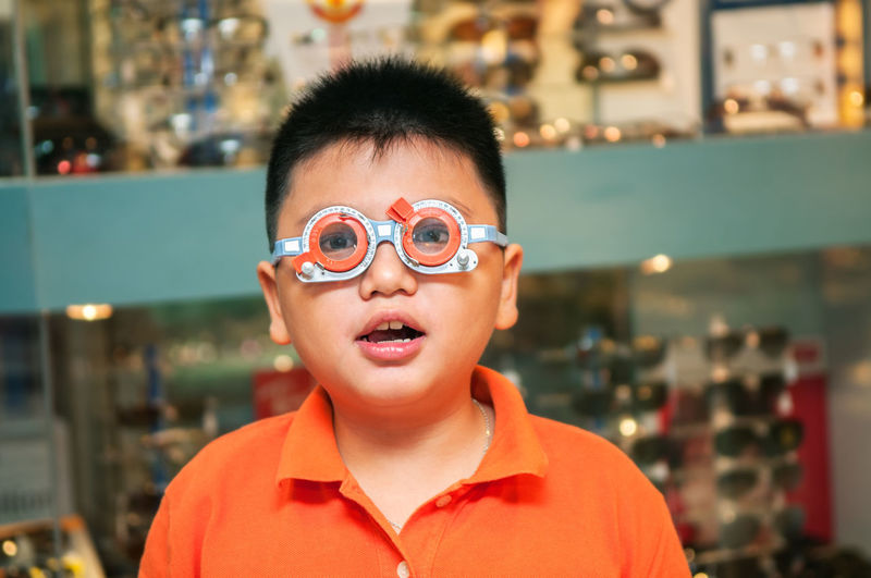 Young boy with trial frame to check vision. 8 Years Old Examination Looking At Camera Boy Casual Clothing Check Up Childhood East Asian Eyecare Eyeglasses  Eyesight Eyesight Test Focus On Foreground Front View Indoors  Kid Myopia Portrait Trial Frame Visual Test