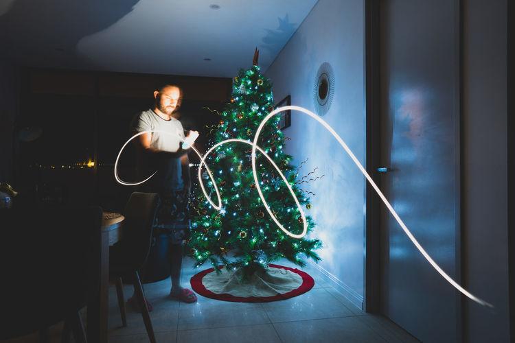 Woman holding illuminated christmas tree at home