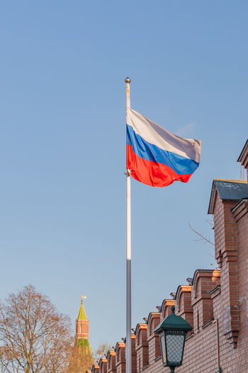 Low angle view of flag against buildings against blue sky