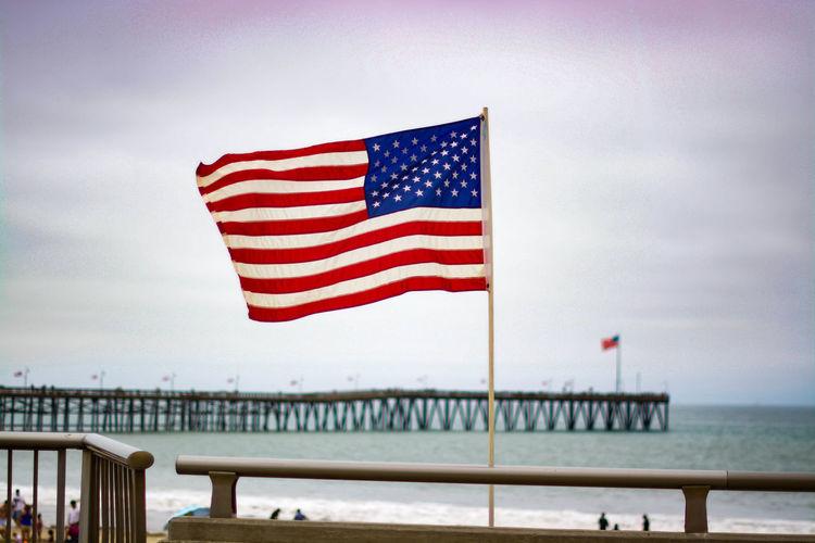 American flag flying on beach against sky