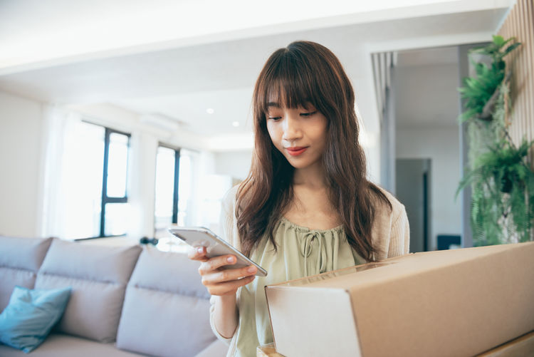 Young woman holding mobile phone at home