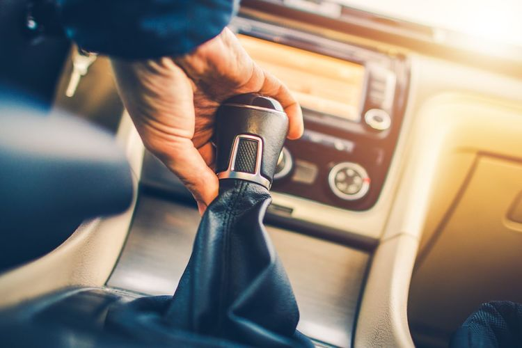 Cropped hand of man holding gearshift while driving car