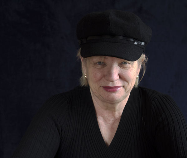 Portrait of smiling mature woman with cap against black background