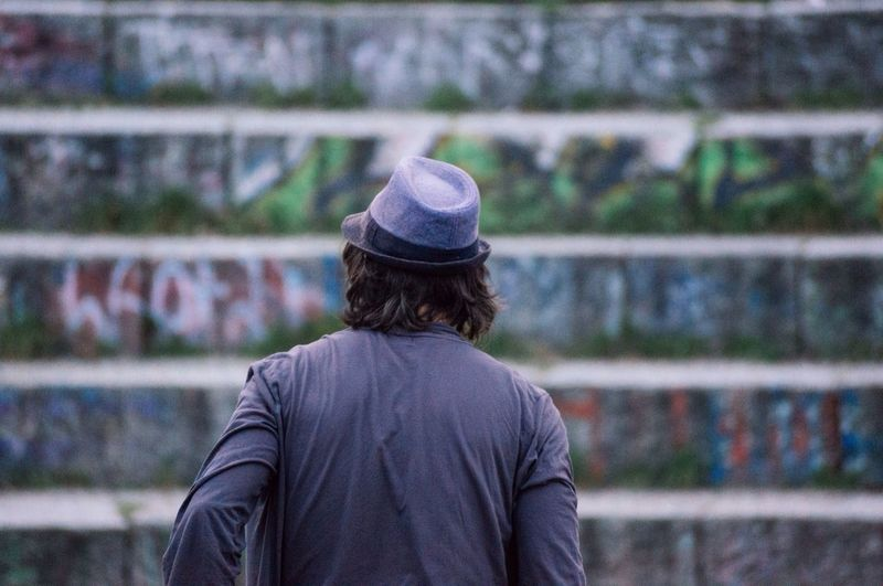 Rear view of man standing against graffiti steps