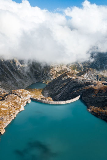 Aerial view of dam amidst mountains against cloudy sky