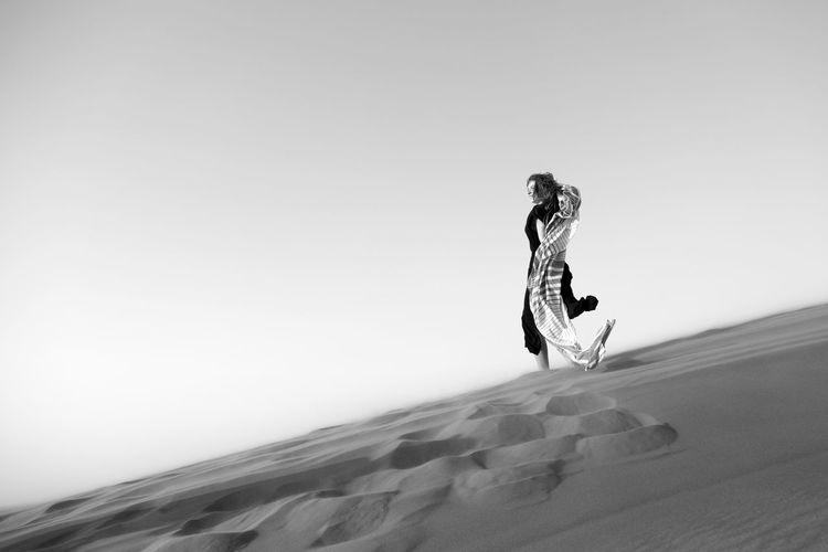 Full length of woman standing in desert against sky
