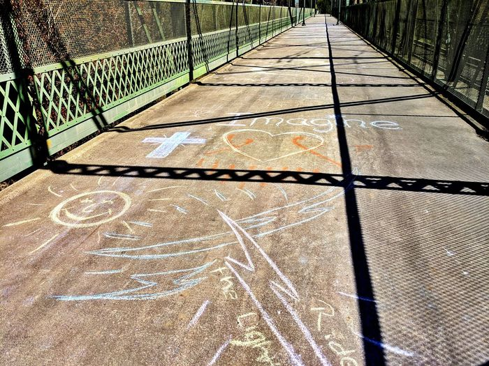 Chalk art on the bridge. After the flood. Keeping spirits high. Imagine. Inspiration. Bridge Chalk Art Imagine Inspiration Flood Spirits Caring Smile Asphalt Shadow Cable Struts Piling Angles Block Green Therapeutic Dark And Light Contrast Diagonal Expression Shadow Sunlight Chainlink Paved Paving Stone Walkway Focus On Shadow Long Shadow - Shadow