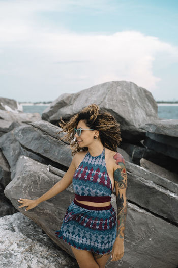Full length of woman on rock at beach against sky