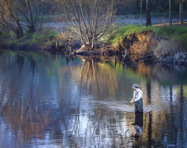Trout fisherman. Bare Tree people and places Full Length Lake Nature Nature Reflection Reflections River Riverbank Scenics Side View Snowy Valleys Shire Stream Tranquil Scene Tranquility Tree Trout Trout Fisherman Tumut Water Waterfront
