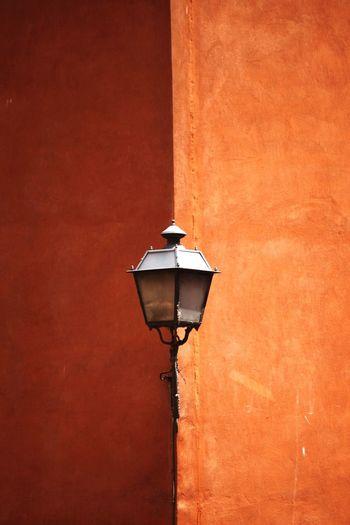 Lamp Post Mounted On Orange Wall