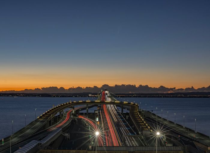 Illuminated Light Trail Transportation Bridge - Man Made Structure Blue Night Sky Outdoors Architecture Water Built Structure Clear Sky No People Sunset Sea Nature