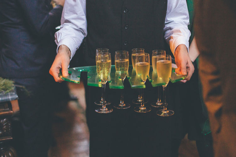 Midsection of waiter carrying champagne