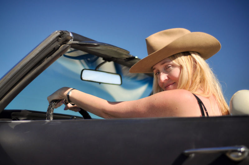 Portrait Hat Blond Hair Beautiful Woman Cowboy Hat Cowgirl Hat Country Western Sky Sunshine Driving Driver Travel Joyride Convertible Car Classic Car Blonde Blonde Girl Smile Smiling Happiness Summer Blue Sky