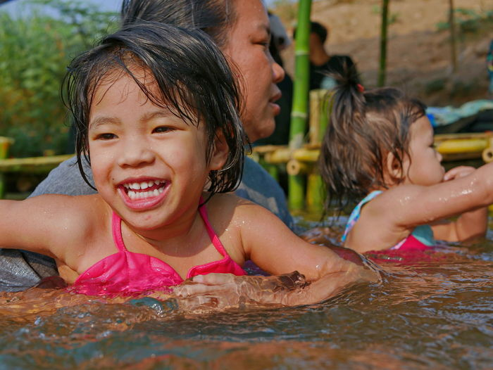Close-up of cute girl sitting at swimming pool