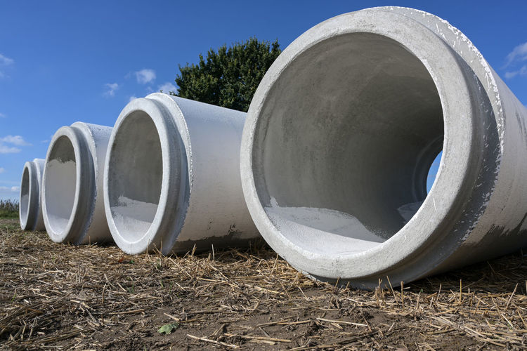 Close-up of pipes on field against sky