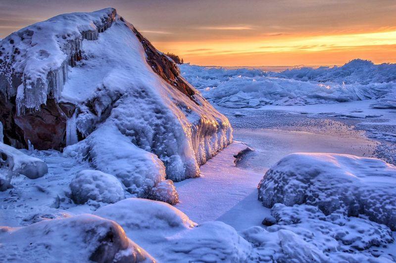 Frozen lake superior against sky during sunrise