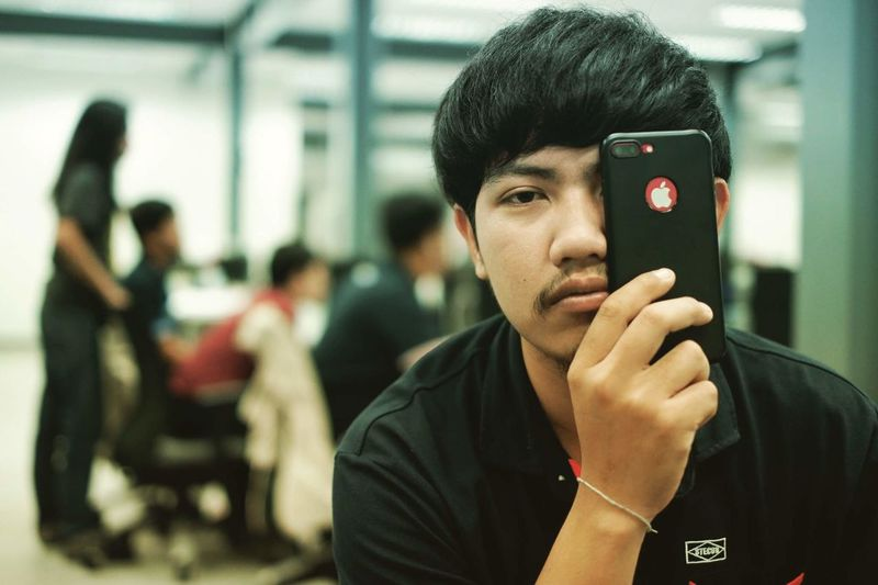 Communication Connection Focus On Foreground Front View Headshot Holding IPhoneography Incidental People Indoors  Lifestyles Mobile Phone One Person Portrait Real People Smart Phone Technology Transportation Wireless Technology Young Adult Young Men