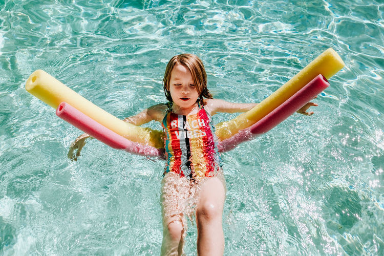 Portrait of happy girl in swimming pool