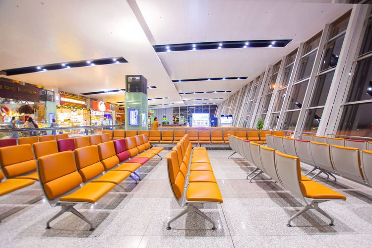 Illuminated Architecture Indoors  Airport Seat Absence Empty Built Structure Modern Ceiling Transportation In A Row No People Lighting Equipment Chair Sign Yellow Public Transportation Airport Departure Area Architectural Column Airport Terminal Tiled Floor