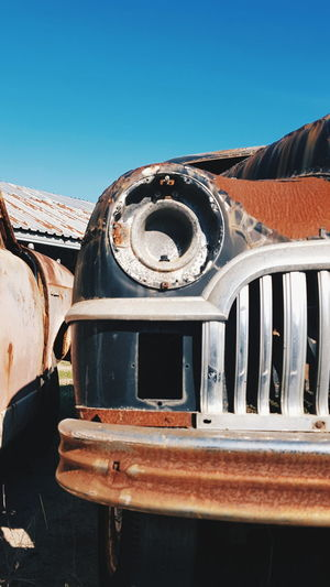 Abandoned truck against clear blue sky old car at scrapyard