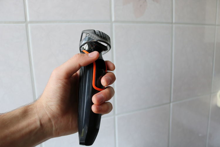 Close-up of man holding electric razor against white tile wall in bathroom