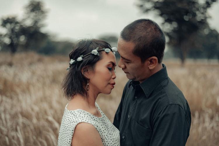 Portrait of couple kissing on field