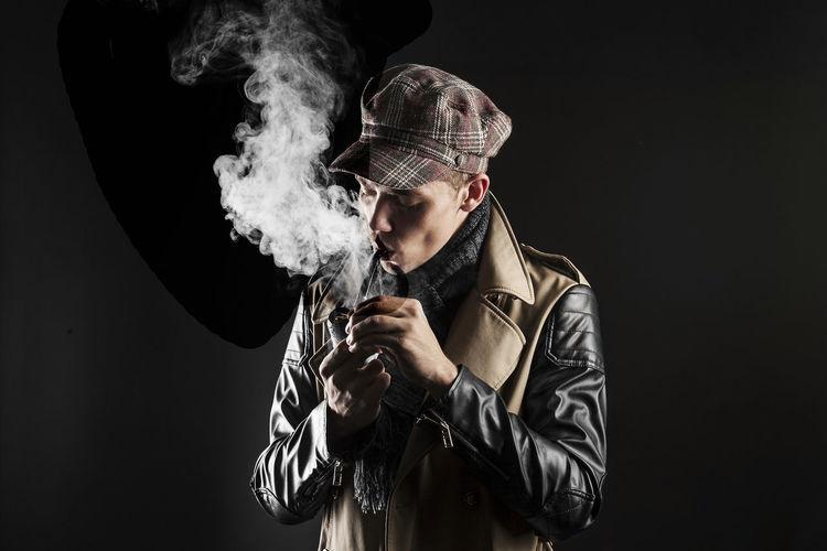 Young man wearing jacket smoking pipe