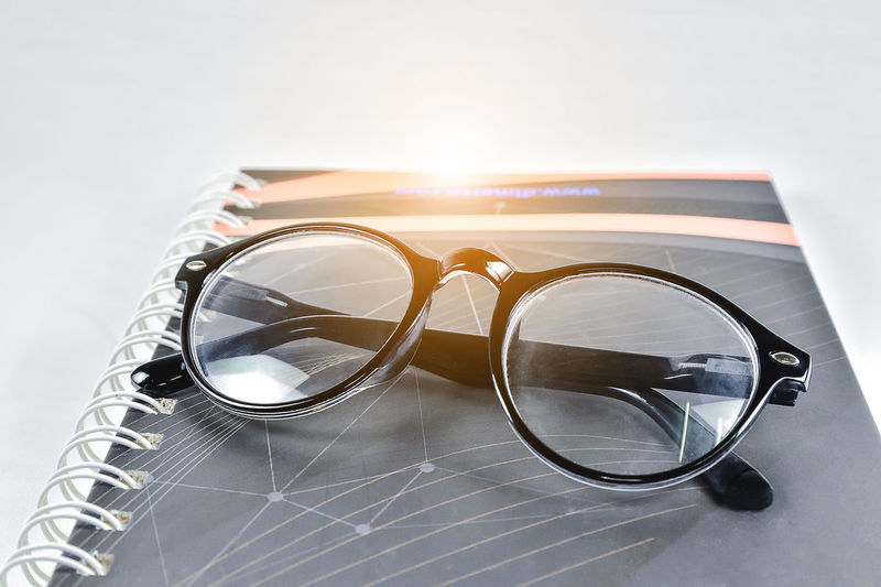 Close-up of eyeglasses on book against white background