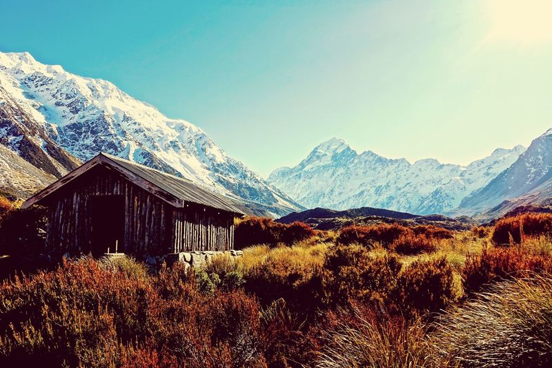 House on field against snowcapped mountain