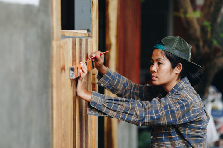 Side view of young female carpenter taking measurement of wood