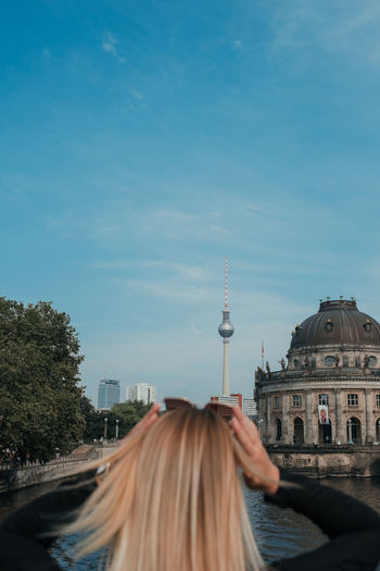 Rear view of woman in city against sky